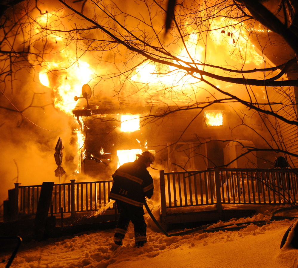 A firefighter attempts to extinguish a stubborn fire Friday that destroyed a home on Northern Avenue in Farmingdale. No injuries were reported, but a dog is missing.