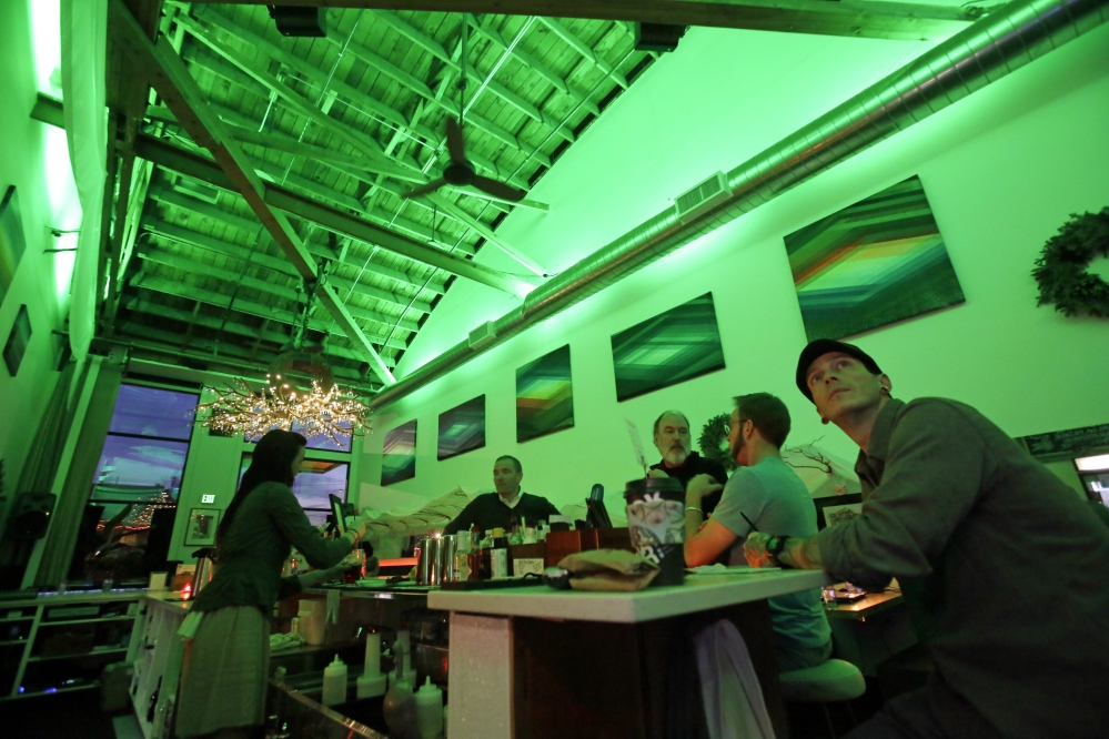 Lightbar patrons sit in a green glow from special lights in Portland, Ore., on Thursday. Designed to mimic sunlight, light boxes help those with seasonal affective disorder.