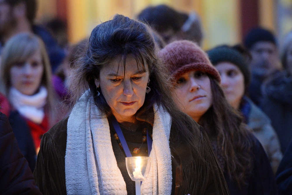 Above, Donna Yellen of the Preble Street Resource Center holds a candle. At right, Rebecca Dennison attends the vigil in memory of her friend, Mary Lou, who died recently.