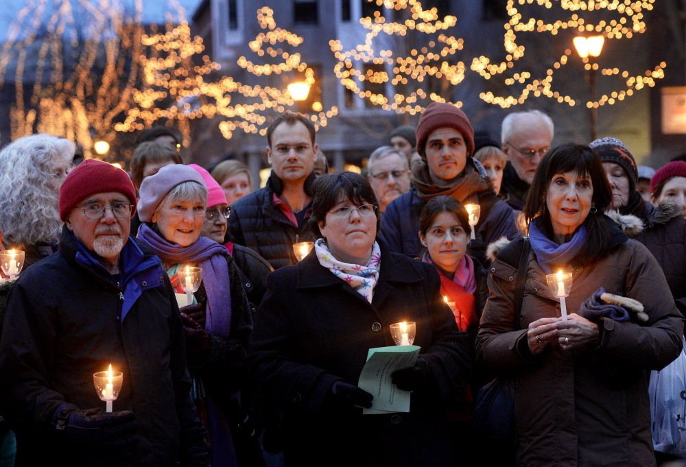 A crowd takes part in the annual memorial vigil for the homeless at Monument Square in Portland on Friday.