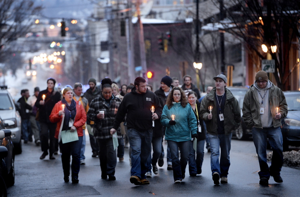 People proceed up Preble Street toward Monument Square in Portland on Friday for the annual memorial vigil. Twenty-one homeless people died while living on the city's streets this year, compared with 30 last year.