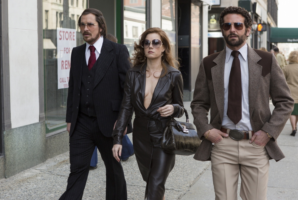 "Christian Bale, left, as Irving Rosenfeld, Amy Adams as Sydney Prosser and Bradley Cooper as FBI agent Richie Dimaso in ""American Hustle."""
