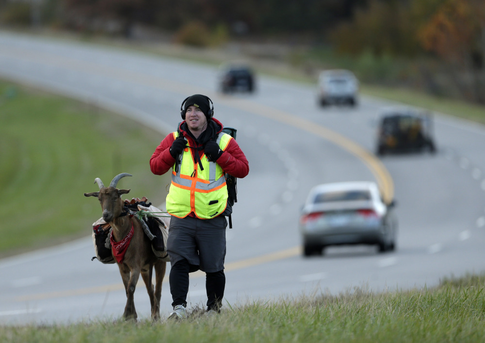 Steven Wescott walks with his goat, LeeRoy Brown, along a street in Lenexa, Kan., last month. The two have been walking since May 2, 2012, from Seattle to New York City to raise money for an orphanage in Kenya.