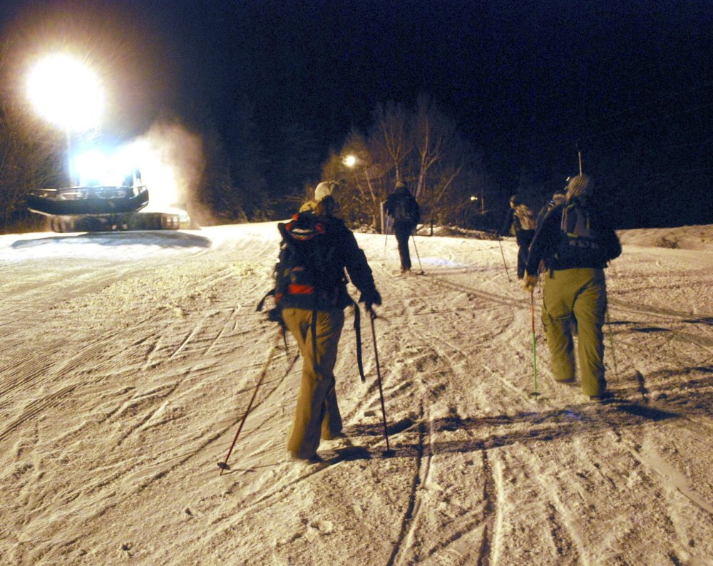 Several skiers head out on the Full Moon Hike up Mt. Abram. At left is a grooming machine that brings their ski equipment up to the top, and from there, well ... it's all downhill.