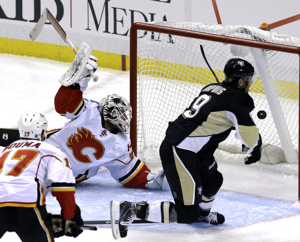 Pittsburgh's Pascal Dupuis has a whole net to put the puck into as Calgary goaltender Karri Ramo is way out of position during Saturday afternoon's game in Pittsburgh.