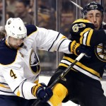 Buffalo's Jamie McBain checks Boston's Brad Marchand into the boards during the second period of Saturday's game in Boston, won by the Bruins 4-1.