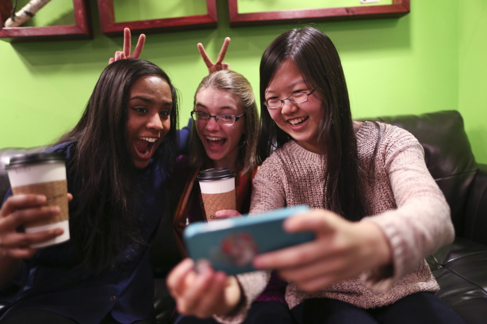 "Amrita Mohanty, 16, from left, Marta Williams, 16, and Michelle Mao, 15, take a Snapchat ""selfie"" while having coffee Dec. 12 at the Steepery Tea Bar in Woodbury, Minn. The ubiquitous smartphone is causing a decline in sales of digital cameras."