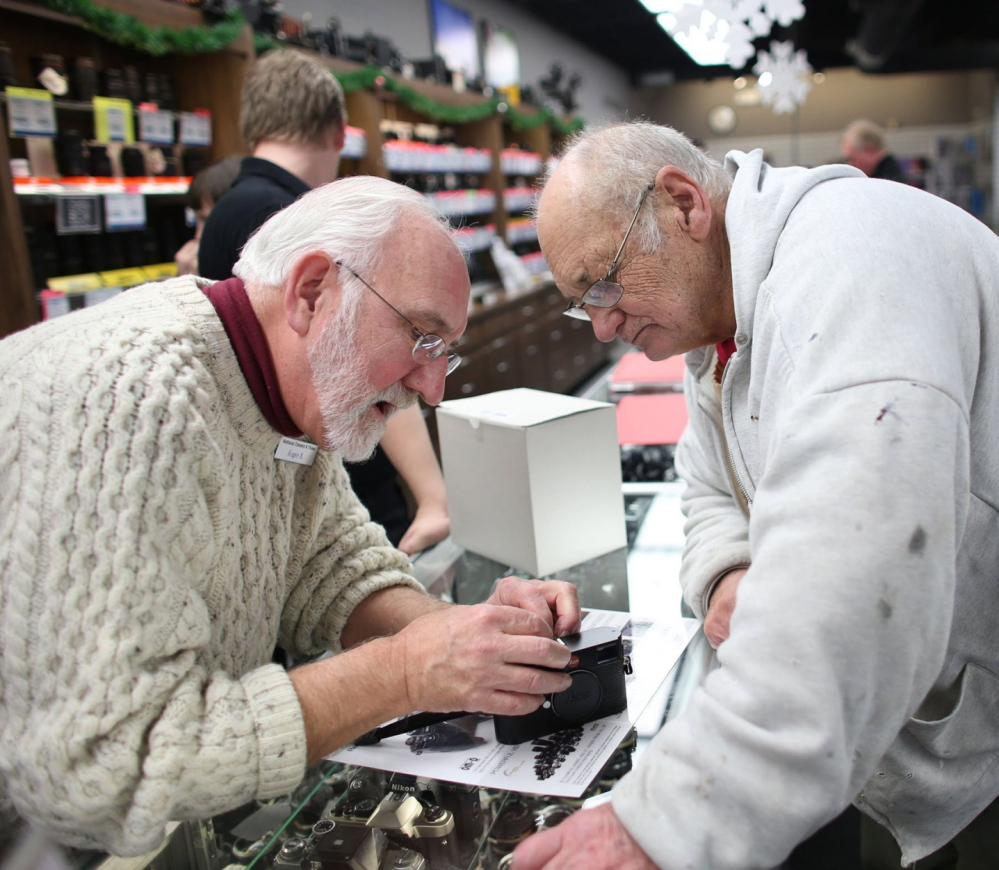 Roger Knight, left, works to set up Wes Sunvold's new digital camera at National Camera Exchange in Golden Valley, Minn.