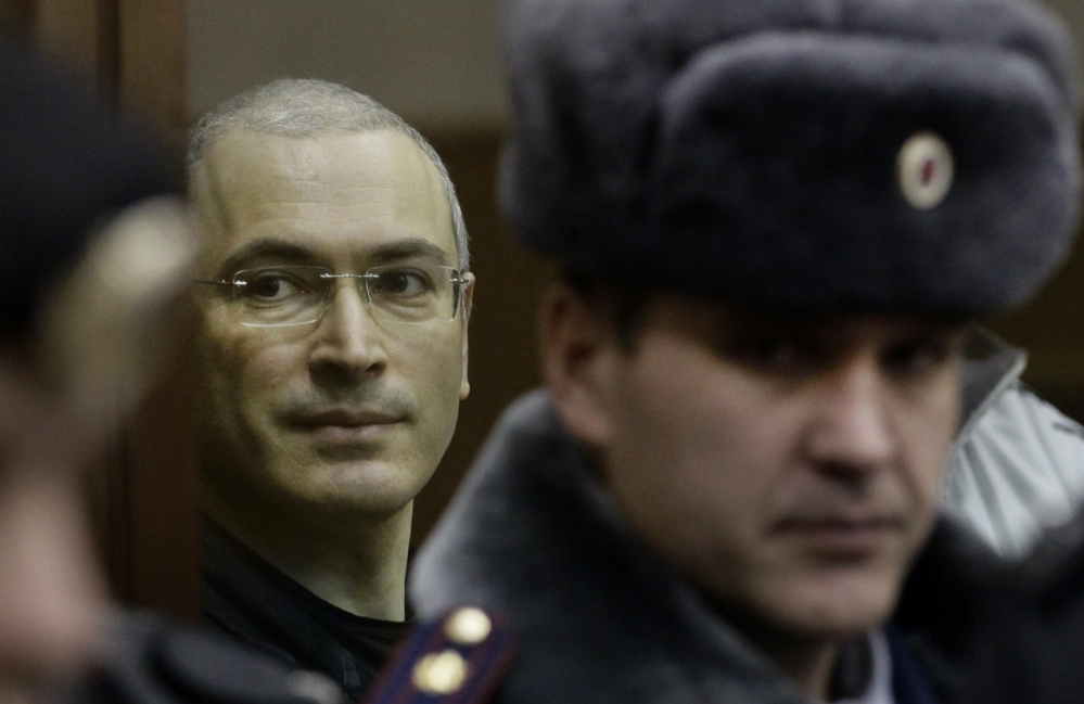 Mikhail Khodorkovsky, left, looks from behind glass in a Moscow courtroom in 2010. Jailed for a decade on tax evasion and embezzlement charges, the former oil baron and Putin critic was released Friday and reunited with his family on Saturday.