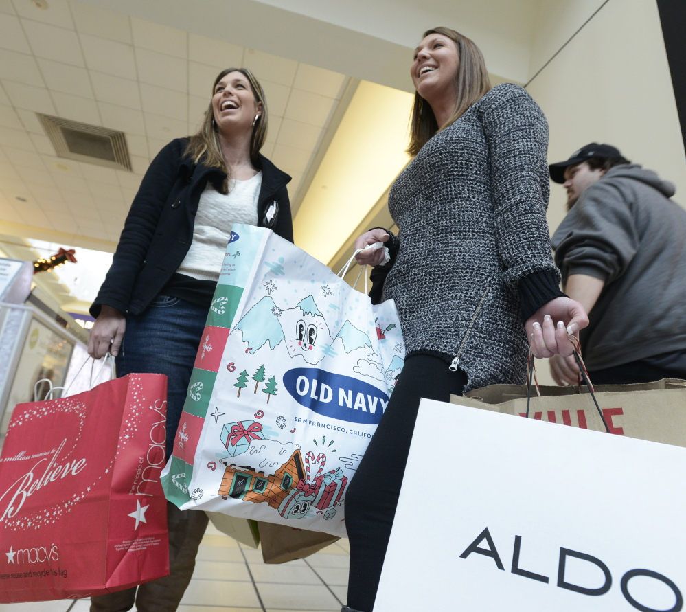 Krysten Harper and Nicole Desmond of Biddeford carry their purchases out of the Maine Mall in South Portland on Saturday.