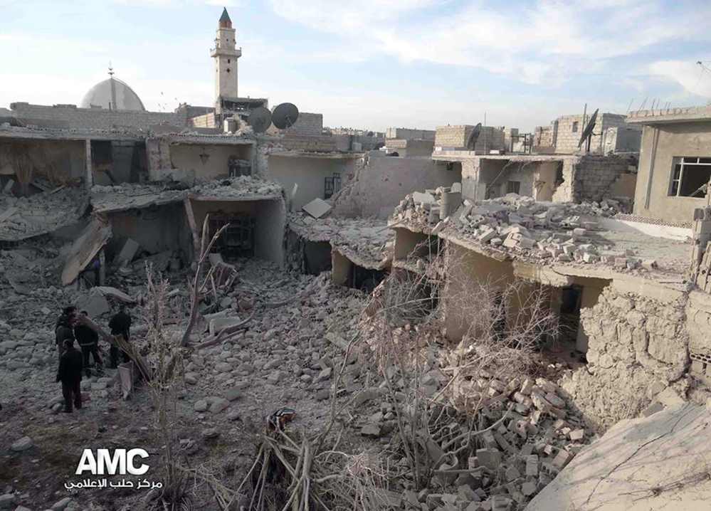 Syrian citizens stand on rubble of houses that were destroyed due to Syrian forces airstrikes in Aleppo, Syria. Syrian government aircraft dumped barrels packed with explosives on at least four opposition-held neighborhoods of Aleppo.