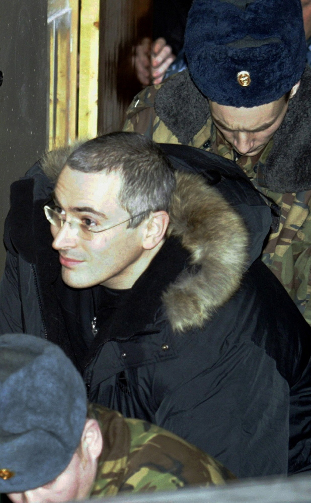 Mikhail Khodorkovsky, who founded Russia's largest oil company and was once the nation's richest man, leaves a Moscow court, escorted by police, in 2003.