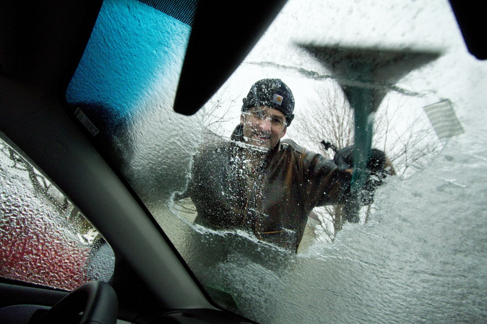 Mark Storck scrapes ice from the windshield of his car in Bridgton on Sunday.