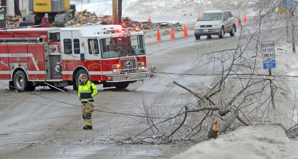 Staff photo by Michael G. Seamans LINES DOWN: The Waterville fire department closed down a section of Main Street in downtown Waterville Monday afternoon after a branch broke under the strain of heavy ice and knocking out power.