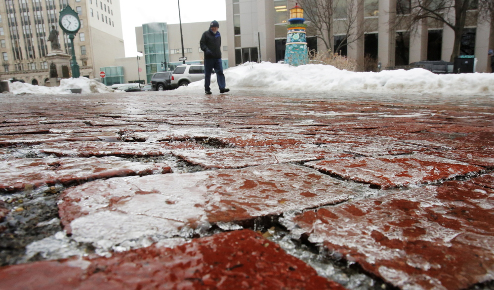 A man walks down the ice-covered brick courtyard of One City Center in Portland on Monday. Sidewalks became coated with ice on Monday, causing pedestrians to shuffle instead of stride through the city.