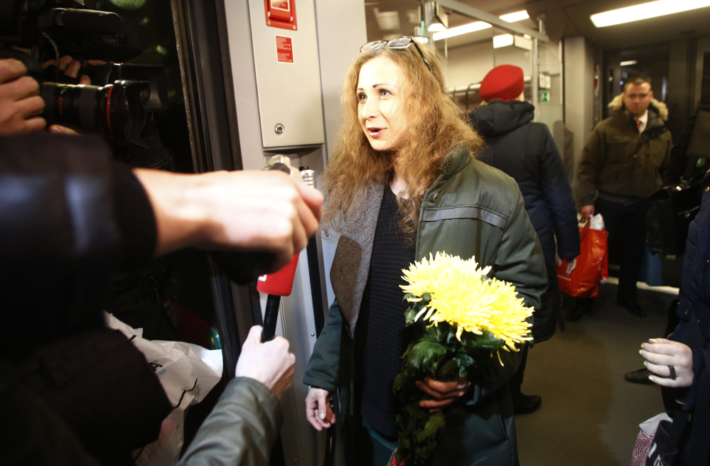 Member of Russian punk band Pussy Riot, Maria Alekhina, speaks to the media while leaving a train upon her arrival in Moscow on Monday. Two jailed Pussy Riot members, Alekhina and Nadezhda Tolokonnikova, were released following an amnesty law that both described as a Kremlin public relations stunt ahead of the Winter Olympics.