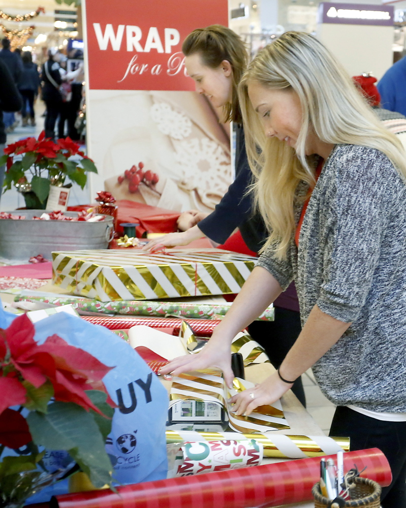 Volunteers Joanna Weathers, foreground, and April Singley, both teachers at the NorthStar Learning Center, wrap gifts Monday for shoppers at The Maine Mall as part of the Wrap for a Reason fundraiser.