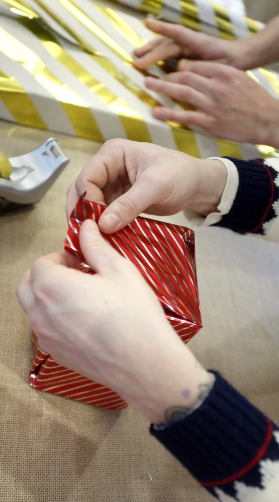 Volunteers wrap gifts for mall customers at The Maine Mall in South Portland Monday afternoon. Monday's donations – as always, encouraged but not required – were earmarked for Easter Seals of Maine. Tim Greenway/Staff Photographer