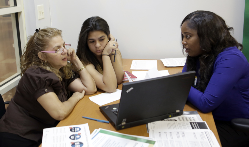 Certified enrollment specialist Richelle Baker, right, talks to Martha Medina, left, and her daughter Martha at a Healthcare Insurance Marketplace office in Miami on Friday.