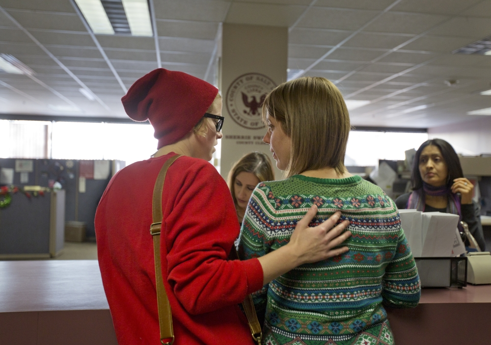 Samantha Christensen, left, and Elise Larsen apply for a marriage license in the Salt Lake County Clerk's Office in Salt Lake City on Friday. A federal judge on Monday is set to consider a request from the state of Utah to block gay weddings that have been taking place since Friday when the state's same-sex marriage ban was overturned.