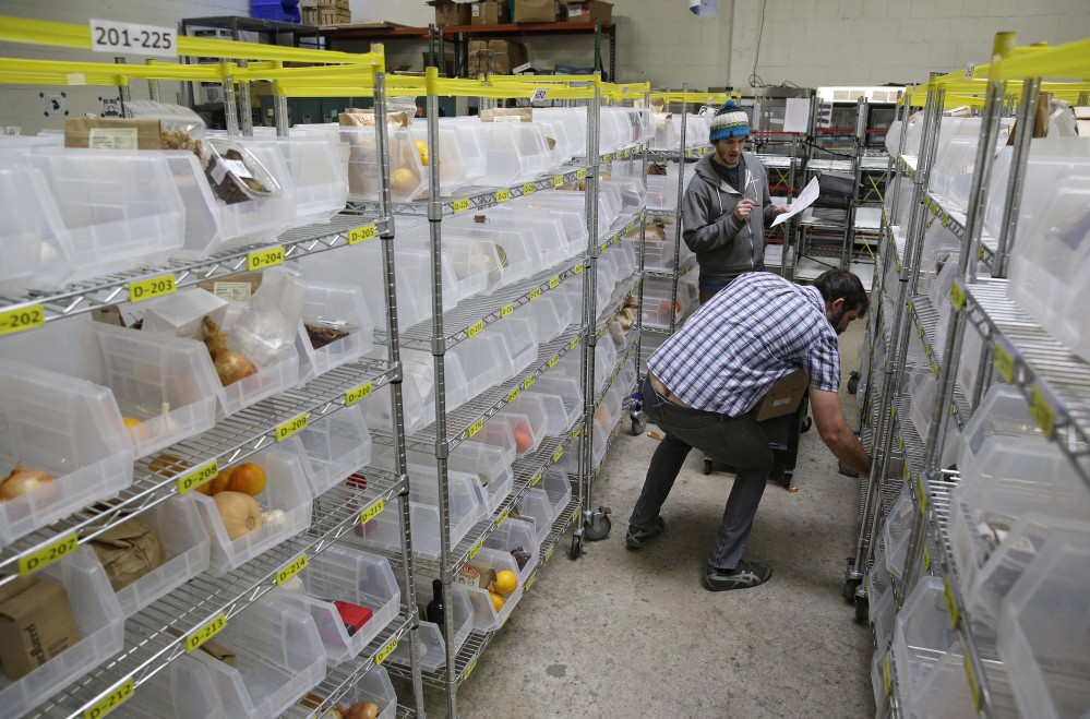 Jesse Hayter, front, and Josh Greenfield fill customer's order bins at the Good Eggs warehouse in San Francisco.