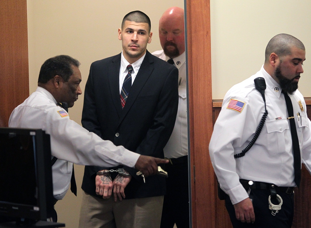 Former New England Patriots NFL football player Aaron Hernandez is led into his court appearance at the Fall River Superior Court in Fall River, Mass., Monday, Dec. 23, 2013. A Massachusetts judge may impose a formal gag order in the murder case against Hernandez, after his attorneys accused the state of allowing leaks that jeopardize his right to a fair trial.
