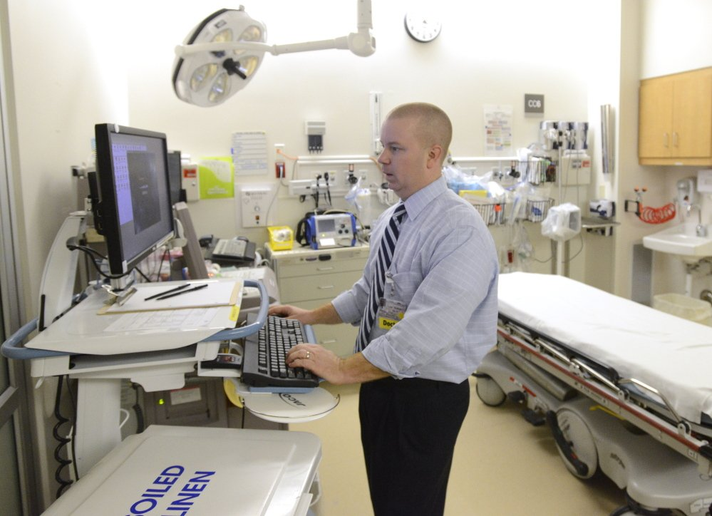 Dr. Nathan Mick of Maine Medical Center uses a new computer system called Epic that makes his work more efficient. Thursday, December 12, 2013. John Patriquin/Staff Photographer.