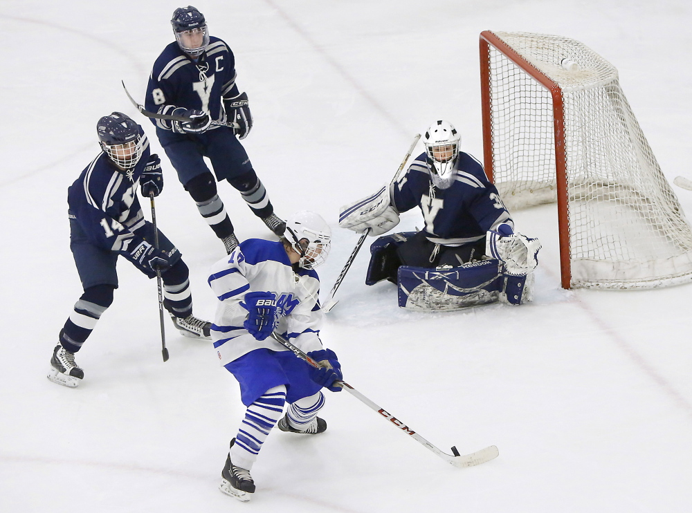James Ross of Kennebunk prepares to take a shot against Yarmouth goalie Nick Allen while Max Watson, left, and Brian Travers defend during a Class B hockey game Monday afternoon at the University of New England's Alfond Forum. The game ended in a 1-1 tie.
