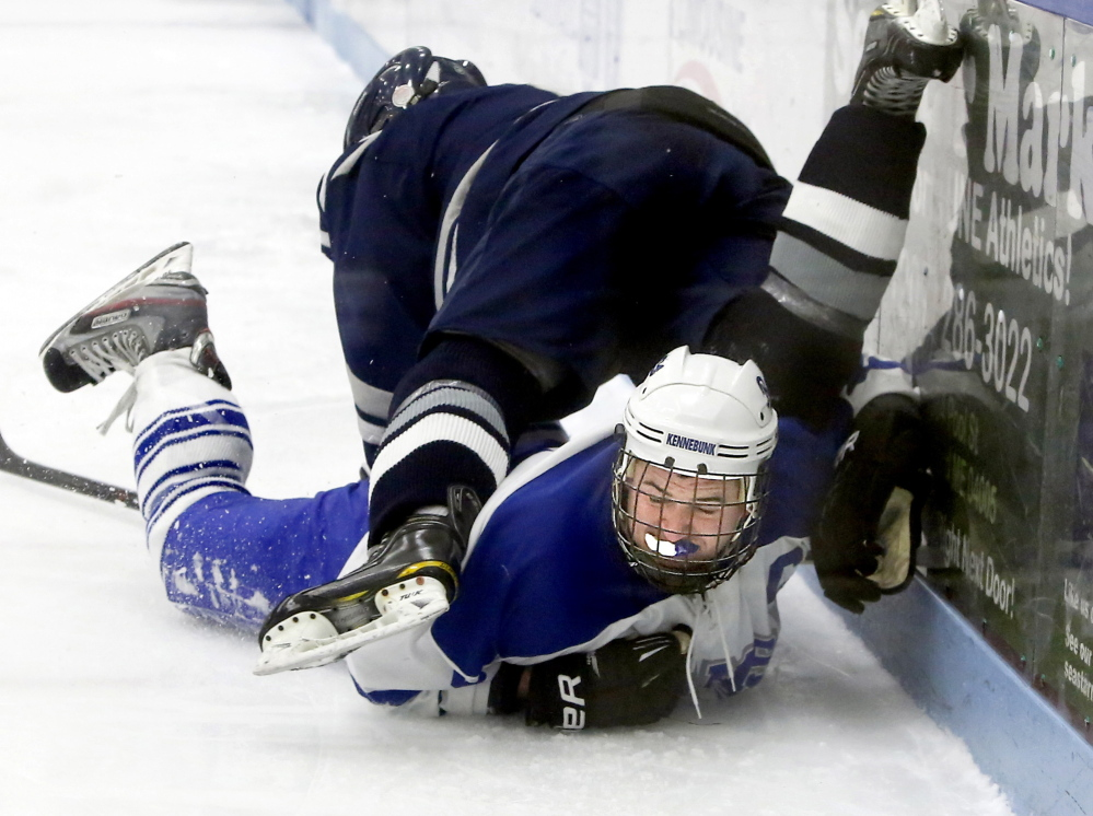 Bryce Fraser of Kennebunk is taken down by a check from Yarmouth's Max Watson, who picked up an assist on his team's only goal.
