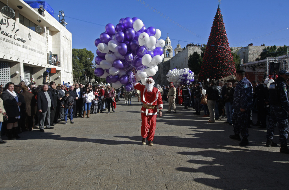 A Palestinian youth dressed as Santa Claus holds balloons at Manger Square, outside the Church of the Nativity, traditionally believed by Christians to be the birthplace of Jesus Christ, in the West Bank town of Bethlehem on Tuesday.