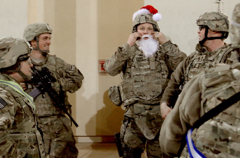 Sgt. Alan Feener of Jefferson adjusts his Santa hat and beard to fit over his body armor as a group of carolers from the 133rd Engineer Battalion of the Maine Army National Guard stopped by some of the barracks at Bagram Air Field in Afghanistan to sing Christmas songs before a church service Tuesday, December 24, 2013.