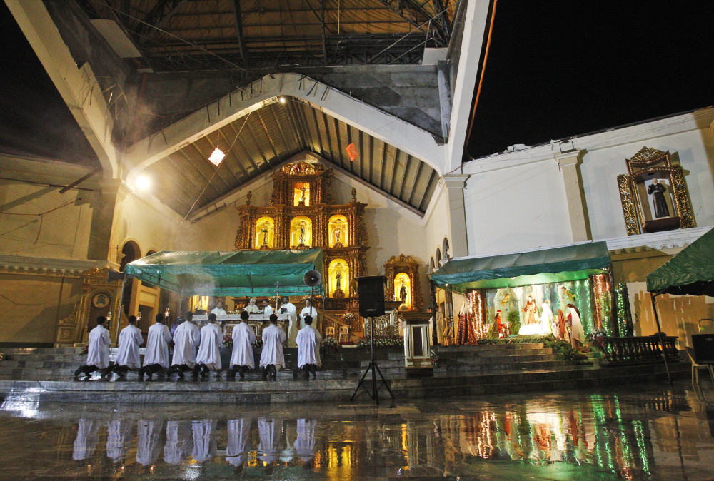 A preacher pray's during final dawn mass on Christmas eve at Palo Cathedral church in Palo, Leyte province in central Philippine, Wednesday.