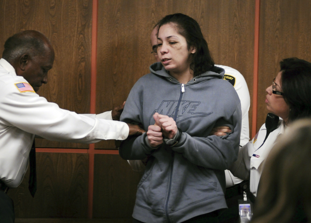 Elsa Oliver is escorted into the courtroom for her arraignment in Fitchburg District Court on Dec. 17, 2013, in Fitchburg, Mass., on charges of reckless endangerment of a child and accessory after the fact of assault in connection with her missing 5-year-old son, Jeremiah Oliver.