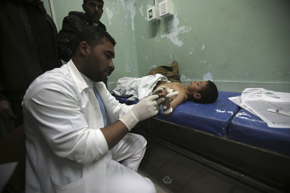 A Palestinian doctor treats a child, who medics said was wounded by shrapnel during an Israeli air strike on the Al Maghazi camp, at treatment room of Al-Aqsa hospital in Deir Al Balah, central Gaza Strip, Tuesday.