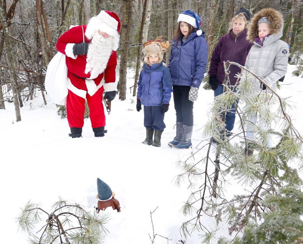 Santa talks to one of his elves as he eads a group of kids and adults on the newly completed sections of the West End Trail in Yarmouth on Tuesday morning to find his elves, Dec. 24, 2013. Tim Greenway/Staff Photographer