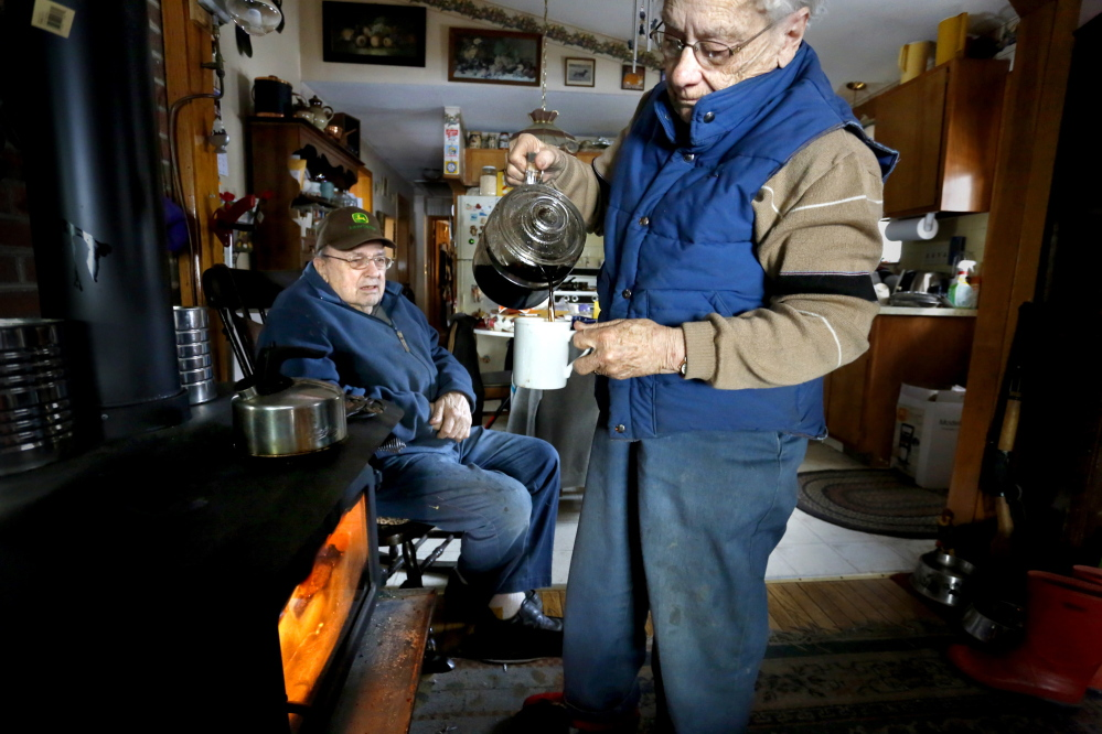 Elsa Seeger pours a cup of coffee that she keeps warm with their wood stove as her husband Robert Seeger warms next to the stove they have been using for heat and cooking when they don't have electricity in their home in Jefferson on Tuesday afternoon, Dec. 24, 2013.