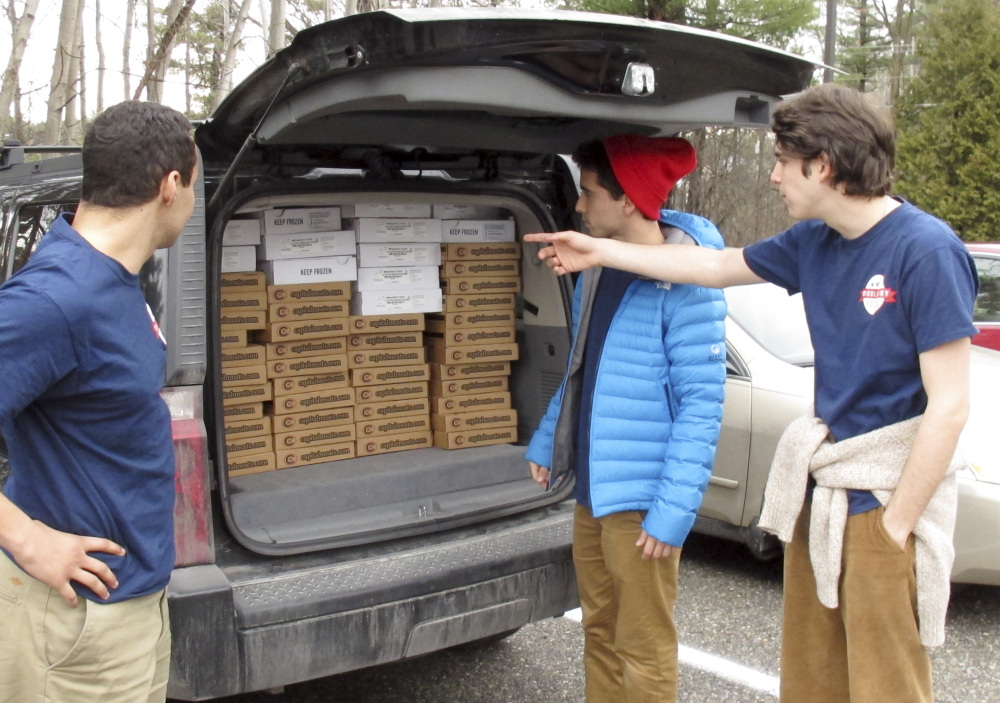 Middlebury College Students Elias Gilman, left, Eddie Danino-Beck, center, and Oliver Mayers prepare to unload frozen meat from the back of a van in Middlebury, Vt.