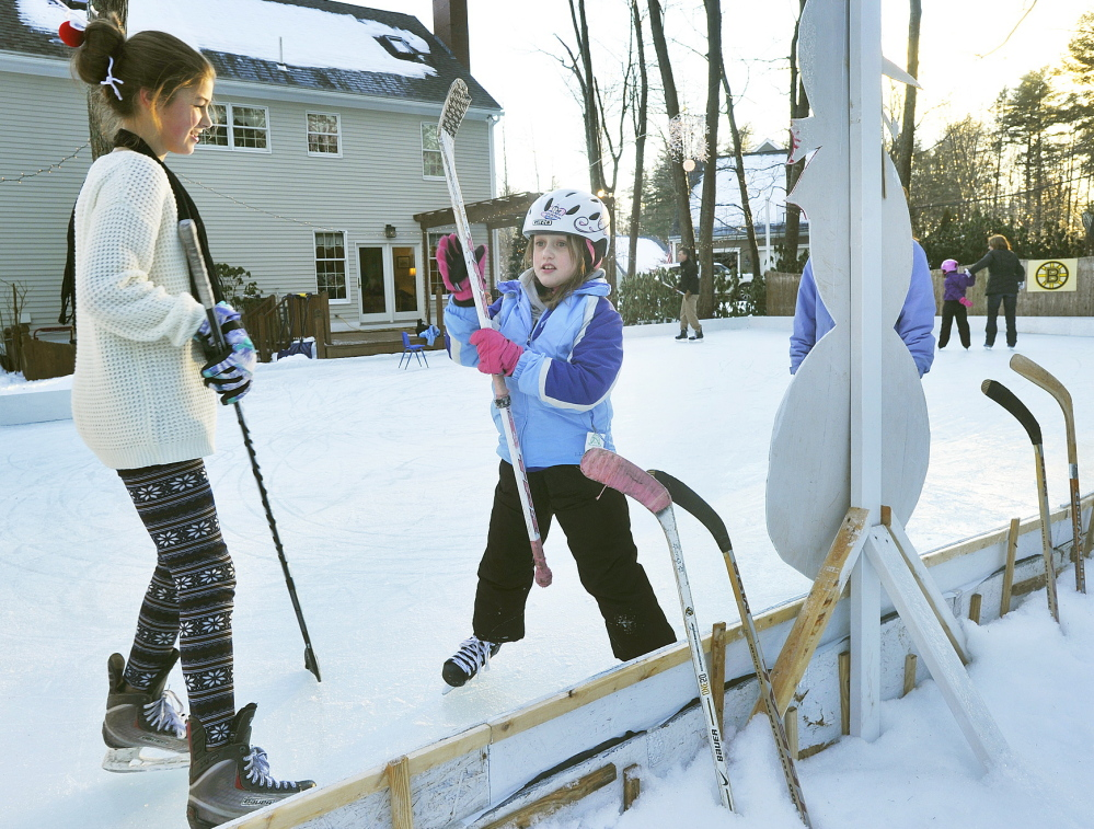 Lauren Topchik helps her cousin Kolby Wohl select a hockey stick during a Christmas Eve skate on the rink that Mike Topchick built in his family's backyard in Scarborough.