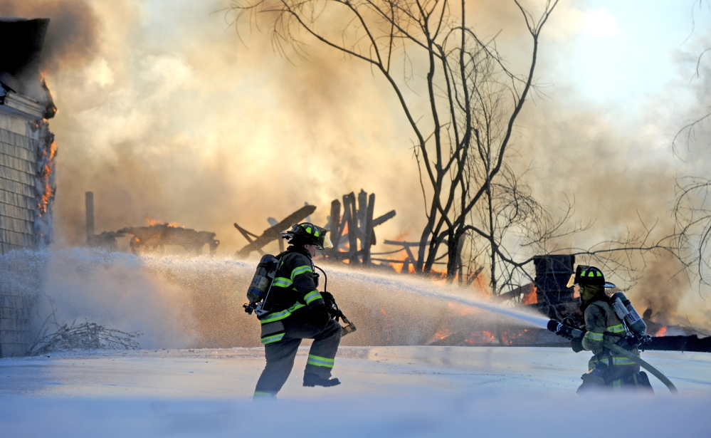 Firefighters battle a fire at 160 Drummond Ave. in Waterville on Wednesday.