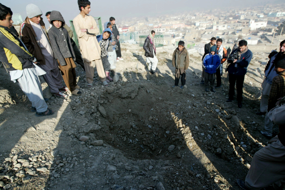 Afghan people stand near a crater from an attack targeting the U.S. embassy in Kabul, Afghanistan, Wednesday, Dec. 25, 2013. The U.S. Embassy in Afghanistan says its compound was hit by indirect fire just before dawn on Christmas Day. It says no Americans were injured.