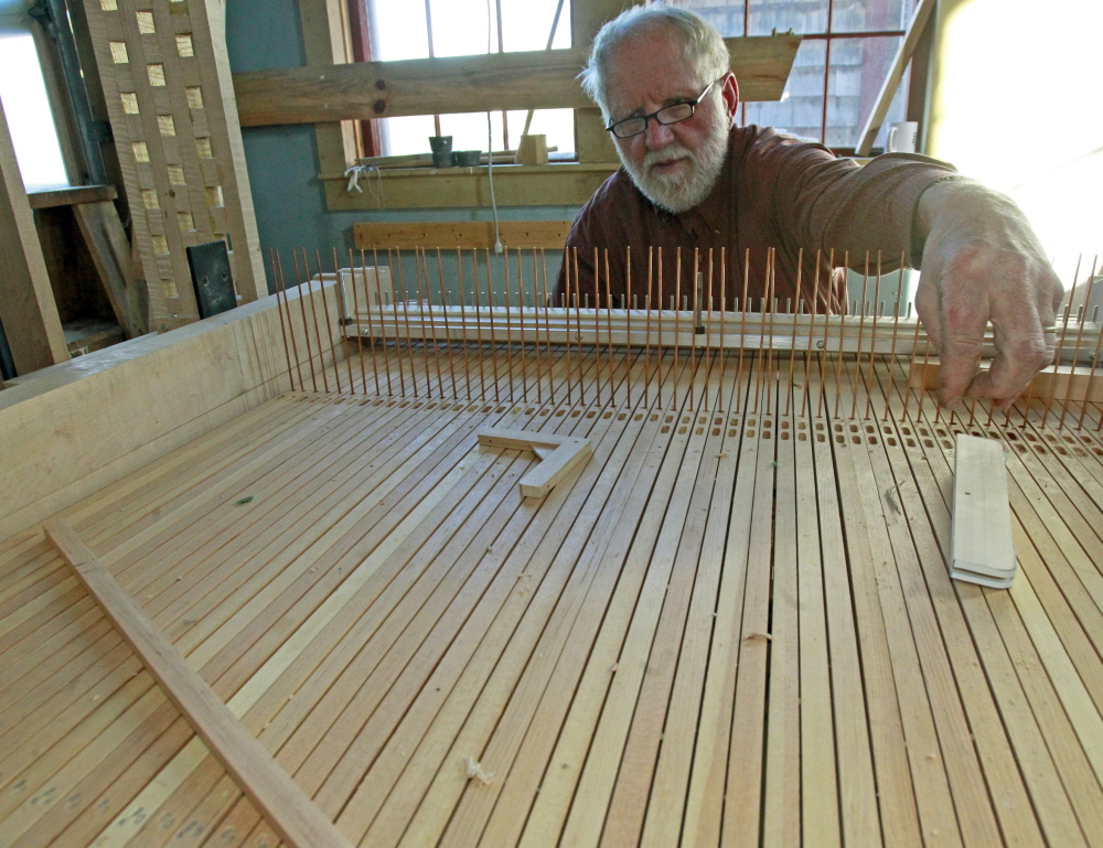 David Moore works on an organ at A. David Moore, Inc., an organ restoration company in Pomfret, Vt. Moore and his six employees generally adhering to a 19th-century construction style when renovating pipe organs, but they use modern-day technology to power the blowers, which provide air to produce the sound.