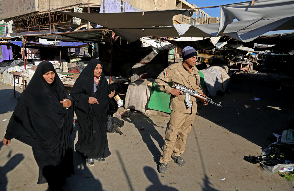 An awakening council member stands guard while women walk through the site of a bombing in a Christian section of Baghdad, Iraq, Wednesday, Dec. 25, 2013. Militants in Iraq targeted Christians in two separate bomb attacks in Baghdad, officials said. The Christmas Day attacks brought the total number of people killed so far this month in Iraq to 441. According to U.N. estimates, more than 8,000 people have been killed since the start of the year.