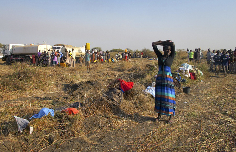 """In this photo taken Tuesday, Dec. 24, 2013 and released by the United Nations Mission in South Sudan (UNMISS) on Wednesday, Dec. 25, 2013, a displaced woman stands by her washing at the U.N. compound where she has sought shelter in Bentiu, in oil-rich Unity state, in South Sudan. In New York, the U.N. Security Council voted unanimously Tuesday to beef up its peacekeeping force in South Sudan and condemned targeted violence against civilians and ethnic communities and called for """"an immediate cessation of hostilities and the immediate opening of a dialogue."""" (AP Photo/UNMISS, Anna Adhikari)"""