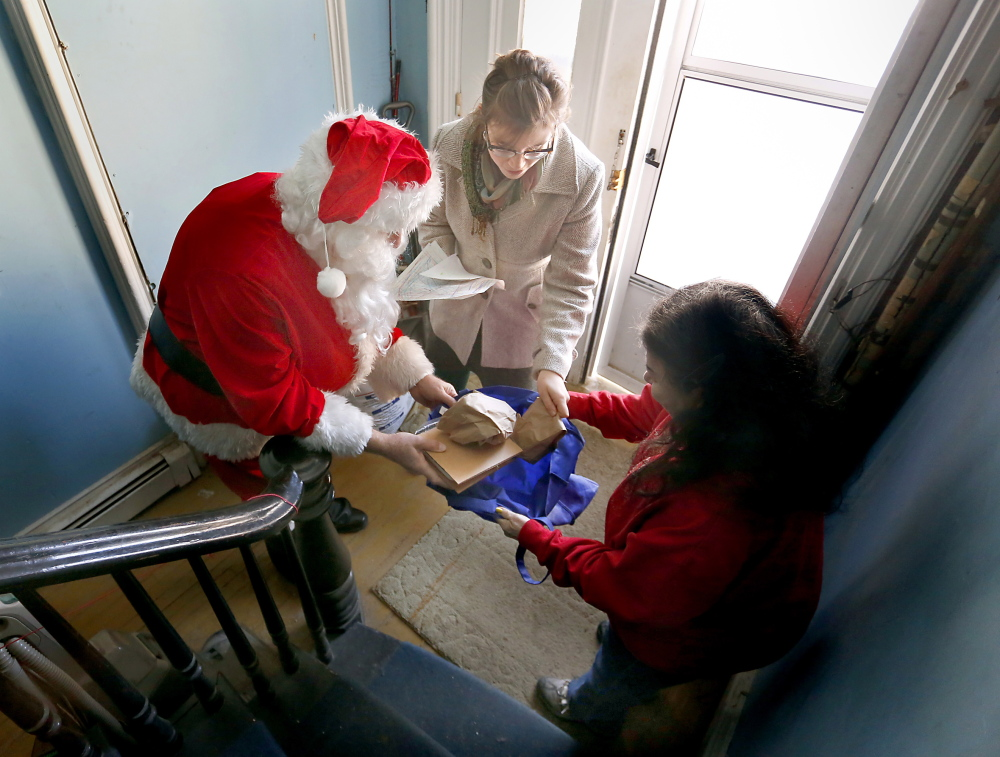 "Philip Rhinelander, dressed as Santa, gives a Christmas dinner to Oscar Yankowsky at his home on Congress Street in Portland. ""It means so much to me,"" said the 80-year-old Yankowsky."