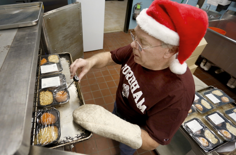 Tom O'Connor of Portland checks the temperature of the meals in the kitchen at the Westbrook Community Center as part of the Southern Maine Agency on Aging's Meals on Wheels program, which delivered hot meals to seniors on Christmas Day.