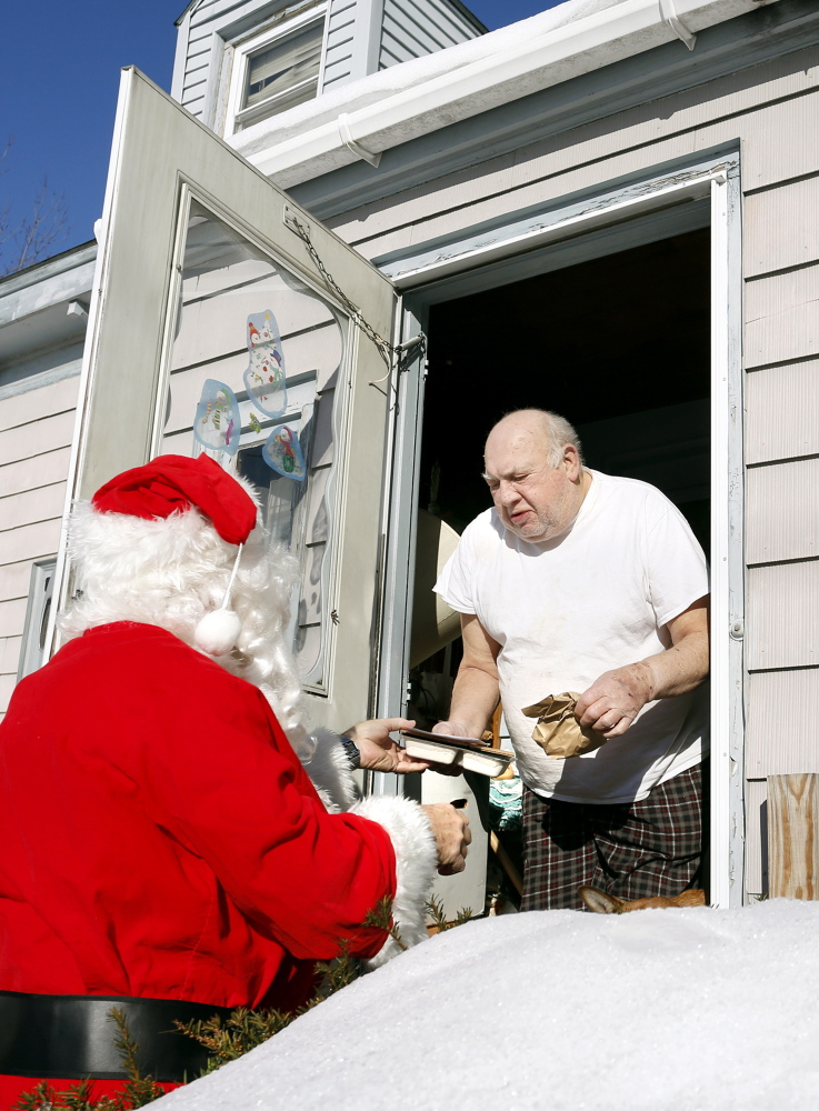 Volunteers Philip Rhinelander and his daughter Julia place food in a bag for Maxine Mooers at her home in Portland as part of the Southern Maine Agency on Aging's Meals on Wheels program, which delivered hot meals to seniors on Christmas Day.