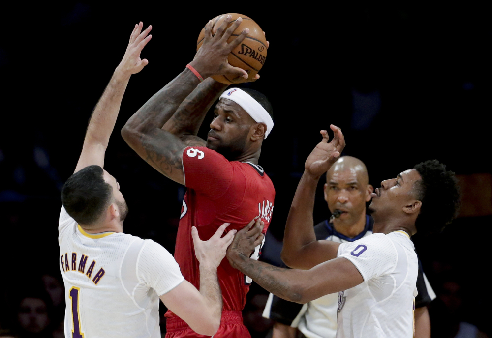 Miami Heat forward LeBron James, middle, is double-teamed by Los Angeles Lakers' Jordan Farmar, left, and Nick Young during a game in Los Angeles on Wednesday.