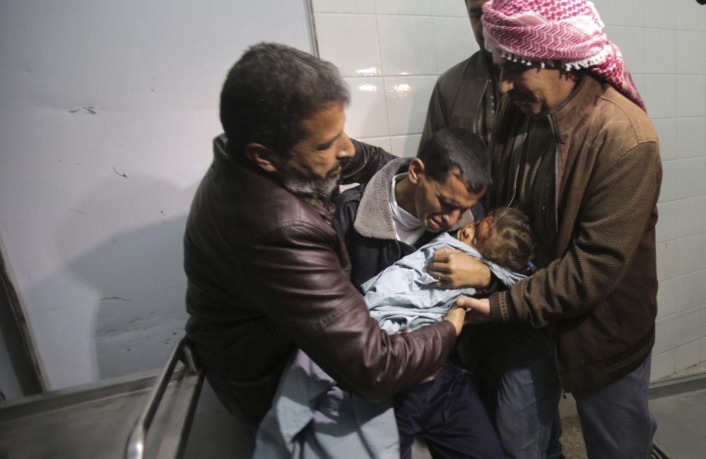 A Palestinian man, center, grieves for his niece, 3-year-old Hala Abu Sebakha, who medics said was killed by shrapnel during an Israeli air strike on the Al Maghazi camp, at the morgue of Al-Aqsa hospital in Deir Al Balah, central Gaza Strip on Tuesday, In response to the deadly shooting of an Israeli civilian by a Palestinian sniper, Israeli air and ground forces launched a series of attacks Tuesday on targets across the Gaza Strip.