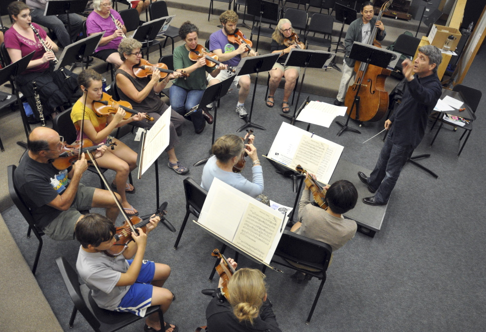 """In this Sept 12, 2013 photo, provided by Me2/Orchestra, Ronald Braunstein conducts a rehearsal of the orchestra in South Burlington, Vt. Bipolar disorder slowed what might have been an explosive career for Braunstein. With his wife, French horn player Caroline Whiddon, Braunstein now runs the Me2/Orchestra, billed as """"the world's only classical music organization for individuals with mental illness and the people who support them."""" (AP Photo/Me2/Orchestra, John Siddle)"""