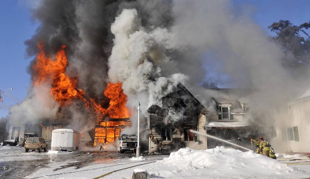 Firefighters from Waterville battle a blaze at 160 Drummond Ave. in Waterville on Wednesday. Officials say the fire was started by woodstove ashes.